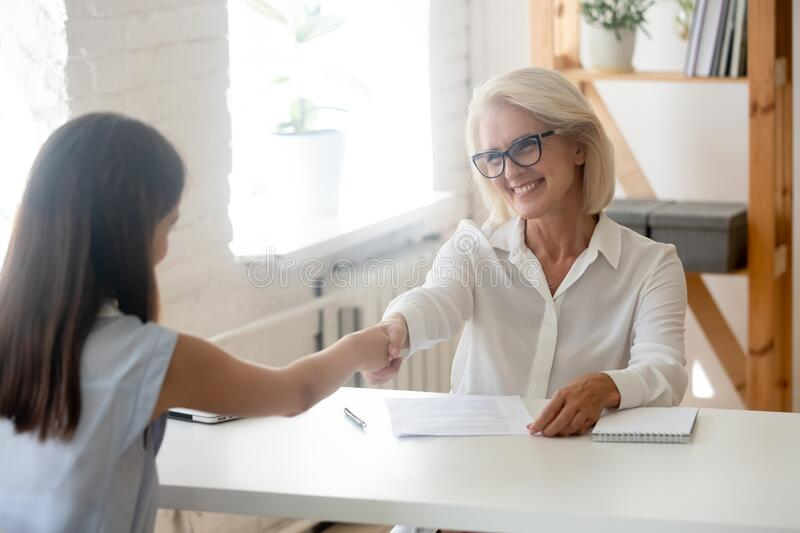 Female hr manager shaking hands with female job applicant stock photo