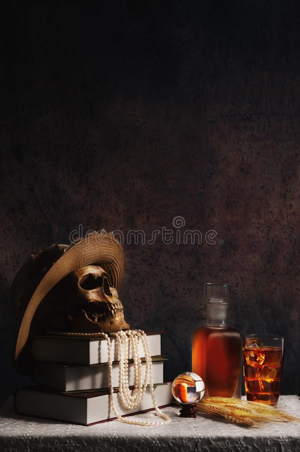 Female humen skull wearing lady style hat with pearl necklace on books placing on table with a glass of ice whisky. Still life of female humen skull wearing lady stock photography