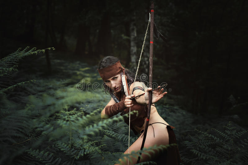 Female hunter aiming with bow stock photo