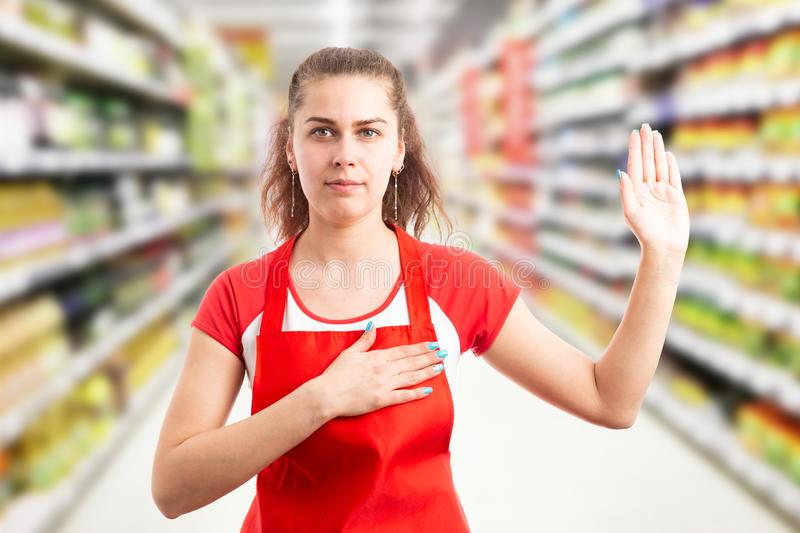 Hypermarket employee making honest oath. Female hypermarket or supermarket employee making honest oath with hand on heart and palm up stock images