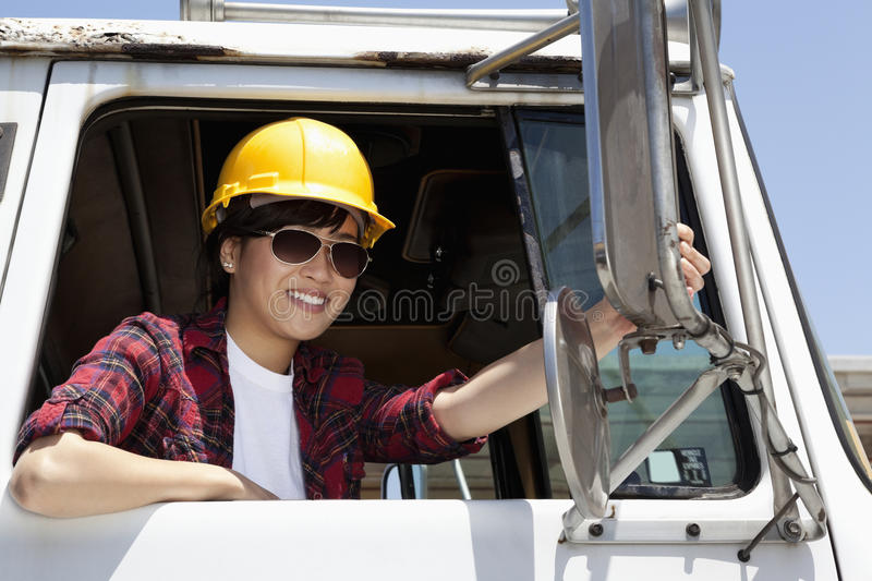 Female industrial worker adjusting mirror while sitting in logging truck stock images