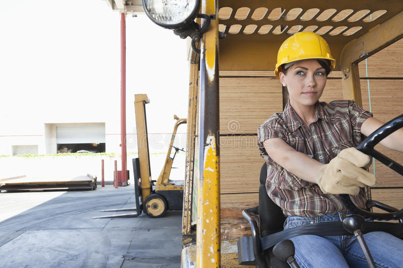 Female industrial worker driving forklift truck royalty free stock image