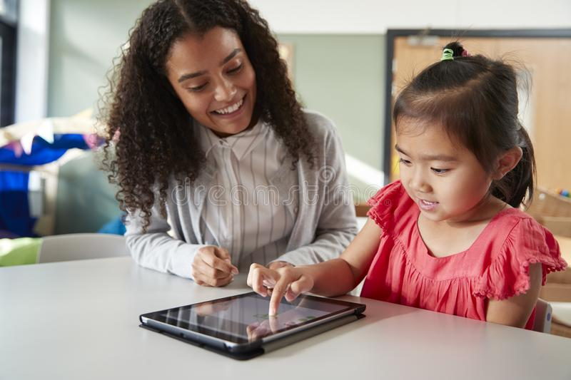 Female infant school teacher working one on one with a Chinese schoolgirl, sitting at a table in a classroom using a tablet comput royalty free stock photo