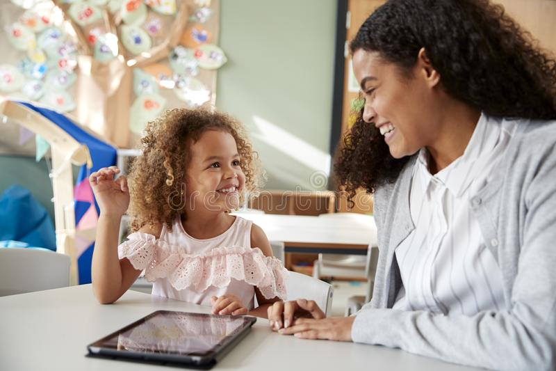 Female infant school teacher working one on one in a classroom using a tablet computer with a young mixed race schoolgirl, smiling royalty free stock images