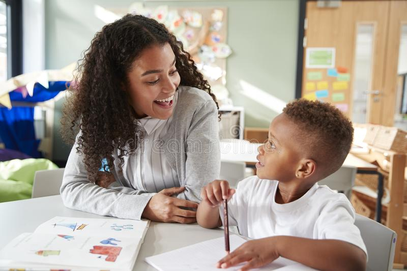 Female infant school teacher working one on one with a young schoolboy, sitting at a table smiling at each other, close up stock image
