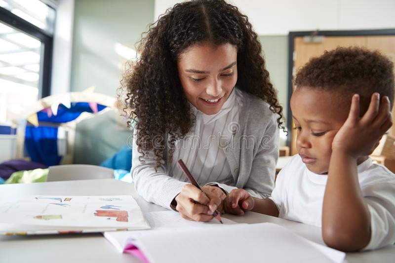Female infant school teacher working one on one with a young schoolboy, sitting at a table writing with him, close up stock image