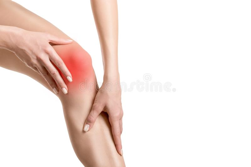 Female injured knee joint. Sore spot highlighted by red marker. Woman touches her leg. Well groomed skin, close up royalty free stock photos