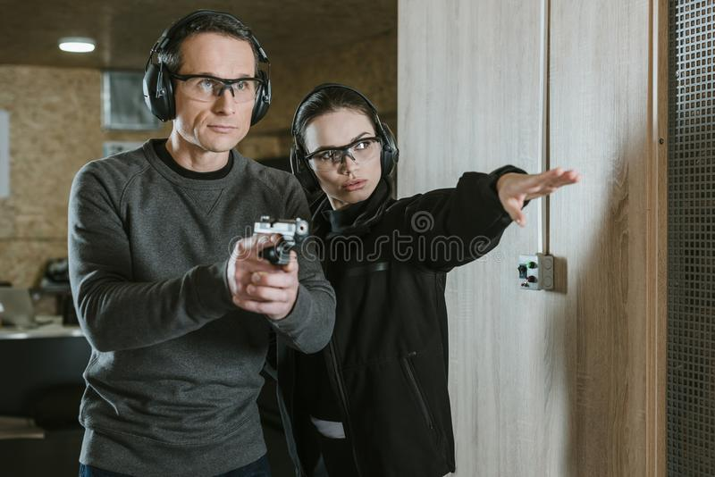 Female instructor showing where shoot to client. In shooting range royalty free stock photography