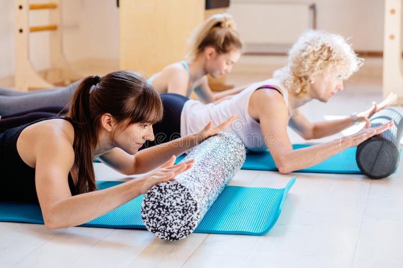 Female instructor workout with foam rollers performing physical pilates exercises together with patients clients in stock photo