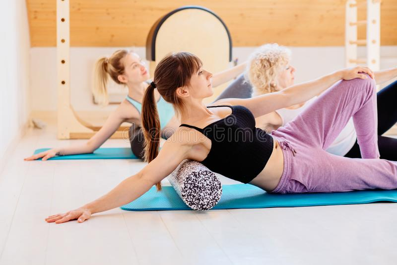 Female instructor with yong female and senior woman together using a foam roller for a myofascial release massage at stock photo
