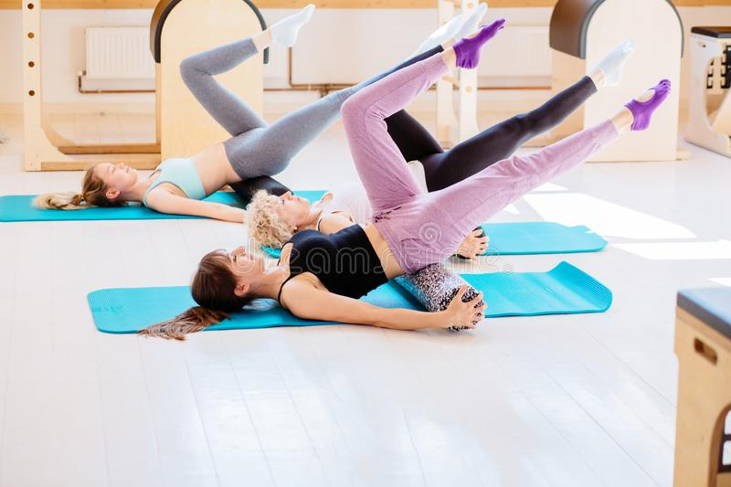 Female instructor with young female and senior woman together using a foam roller for a myofascial release massage at stock photos