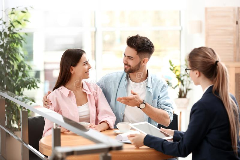 Female insurance agent working with young couple. In office stock photography