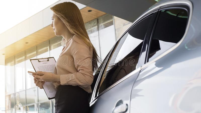 Female insurance broker holding contract and waiting for client near automobile. Stock photo stock images
