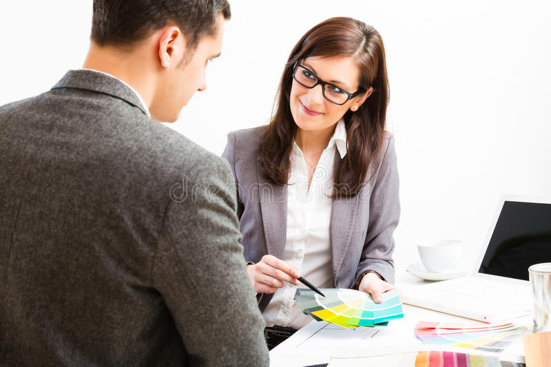 Female Interior Designer With Client. Female interior designer talking to her client royalty free stock images
