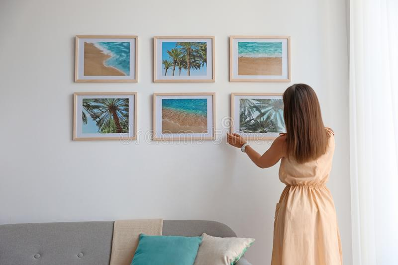 Female interior designer decorating white wall with pictures. Indoors royalty free stock images