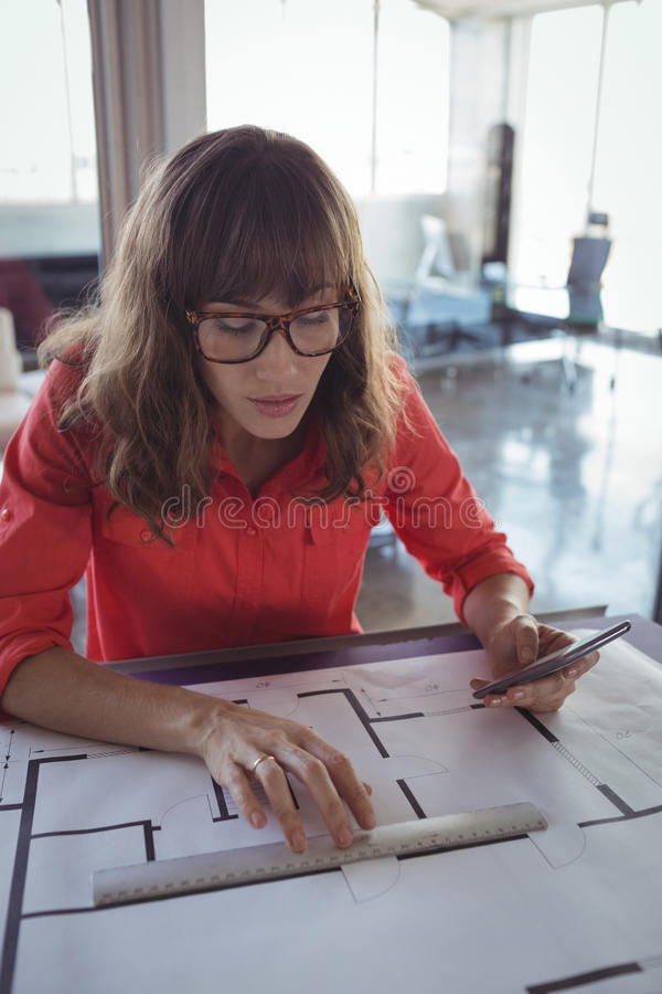 Female interior designer drawing on papers in office royalty free stock images