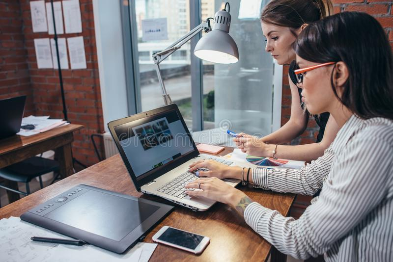 Female interior designer working with a customer watching pictures using laptop sitting at modern studio royalty free stock image