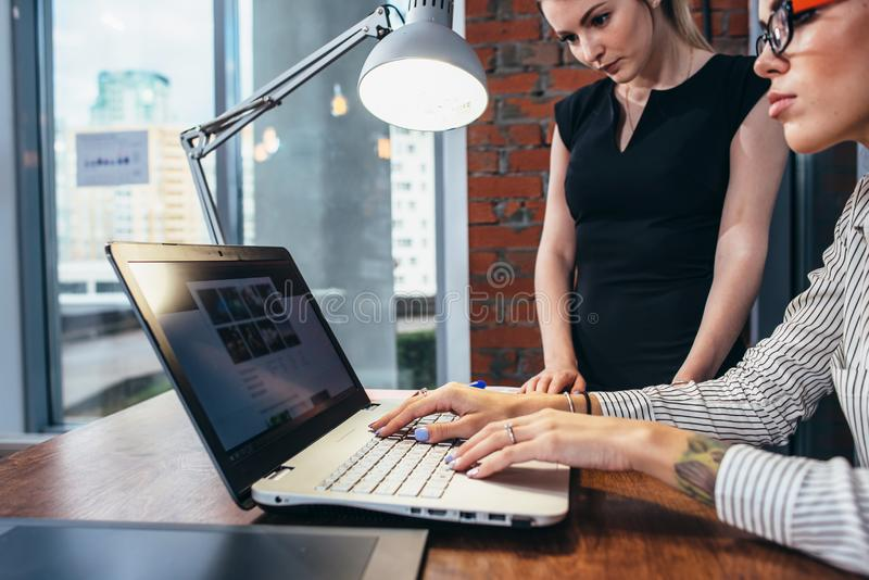 Female interior designer working with a customer watching pictures using laptop sitting at modern studio.  stock image