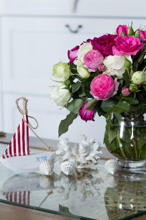 Interior in hampton style - fresh flowers, shells, sailboat decorations. Female interior in hampton style - fresh flowers, shells, sailboat decorations stock image