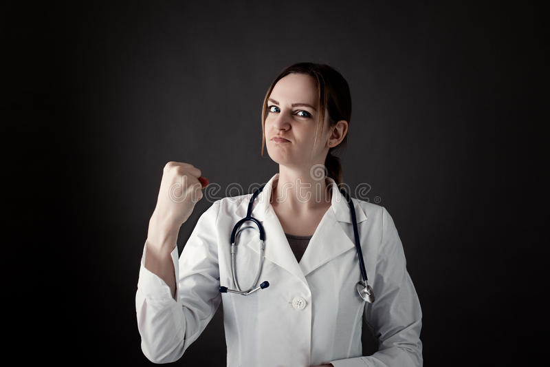Female Intern Holds a fist and look in camera with strong face. Stethoscope or phonendoscope on neck. Medicine photo. Medical care or insurance concept stock image