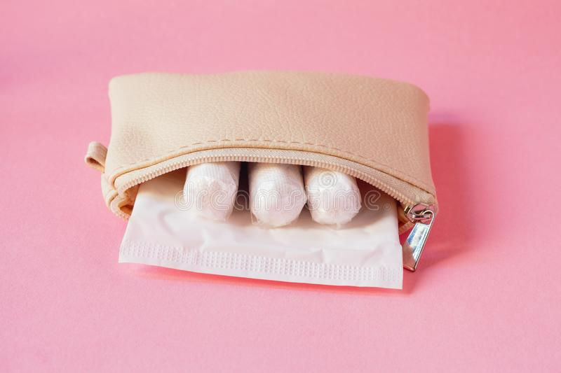 Intimate hygiene products - sanitary pad and tampons in white handbag on pink background. Female intimate hygiene products - sanitary pad and tampons in white royalty free stock photo