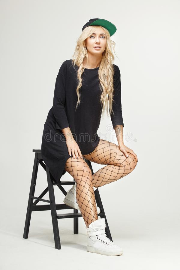 Female isolated portrait of stylish blonde swag sitting on chair at white background. fashion, trends, look. Beautiful girl in fashionable clothes royalty free stock images