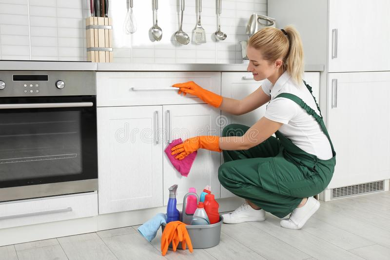 Female janitor cleaning cabinet with rag royalty free stock photo