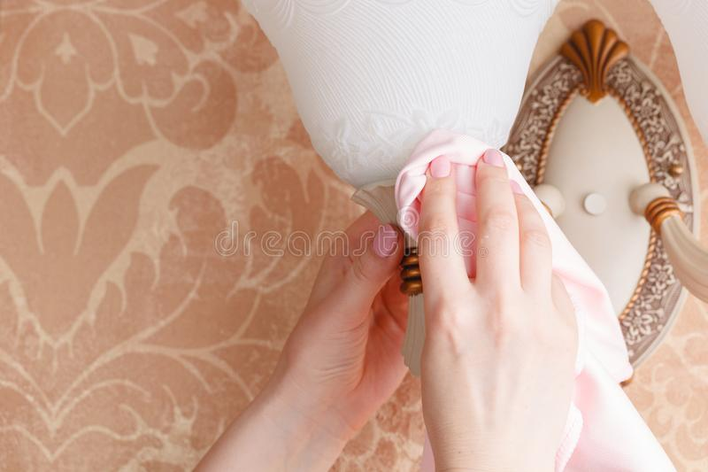 Female Janitor Cleaning Electric Light At Home royalty free stock images