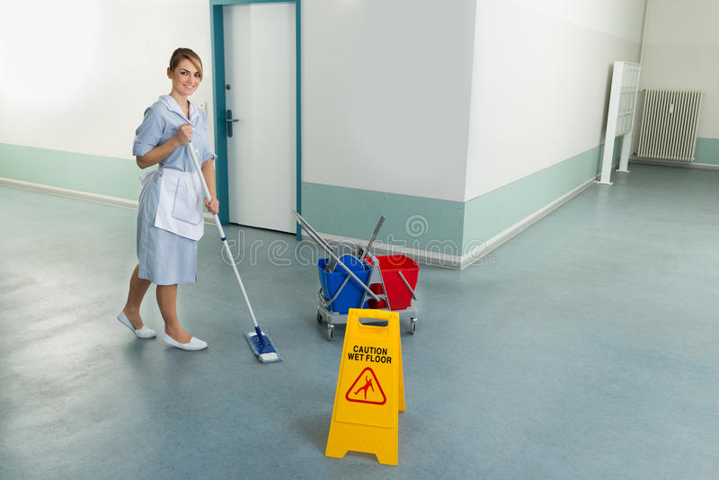 Female janitor cleaning floor stock images