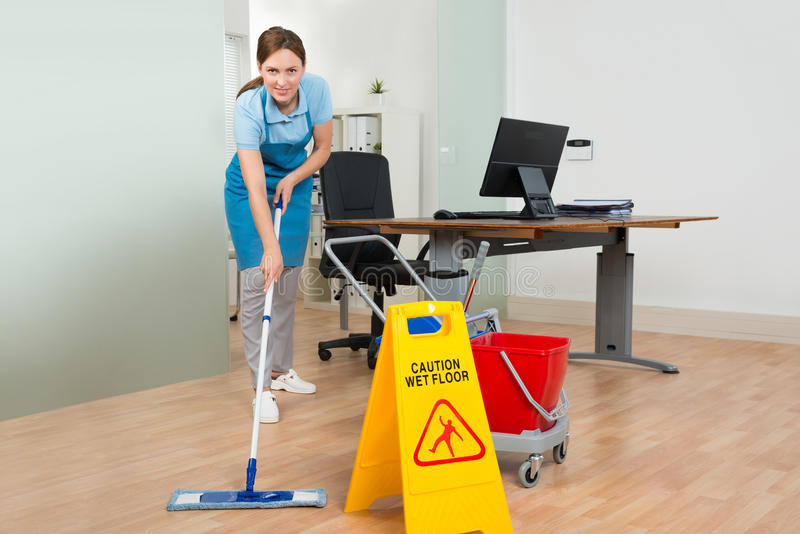 Female Janitor Cleaning Hardwood Floor In Office stock images