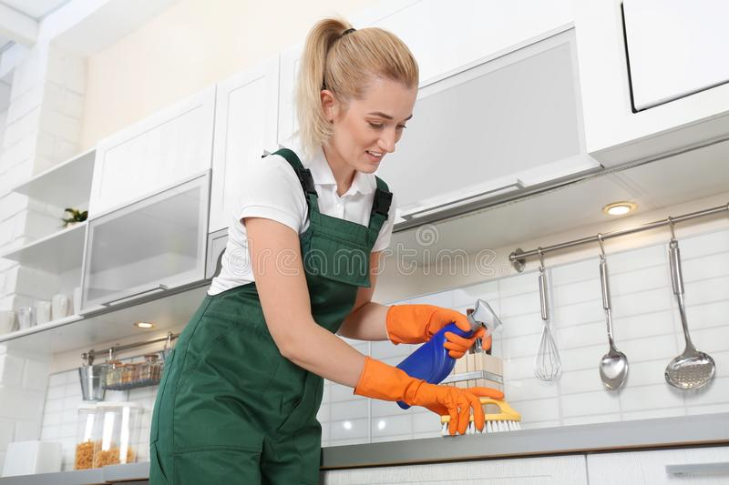 Female janitor cleaning kitchen counter with brush royalty free stock image