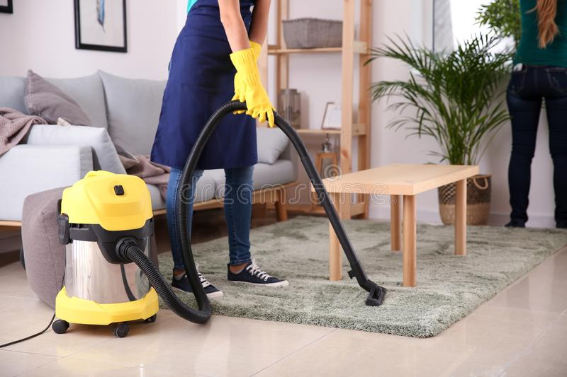 Female janitor hoovering carpet in flat stock image