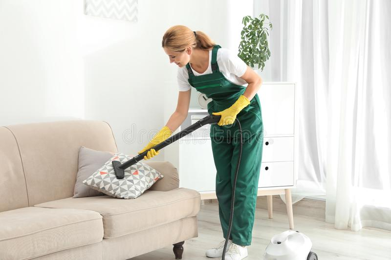 Female janitor removing dirt from sofa cushion royalty free stock photos