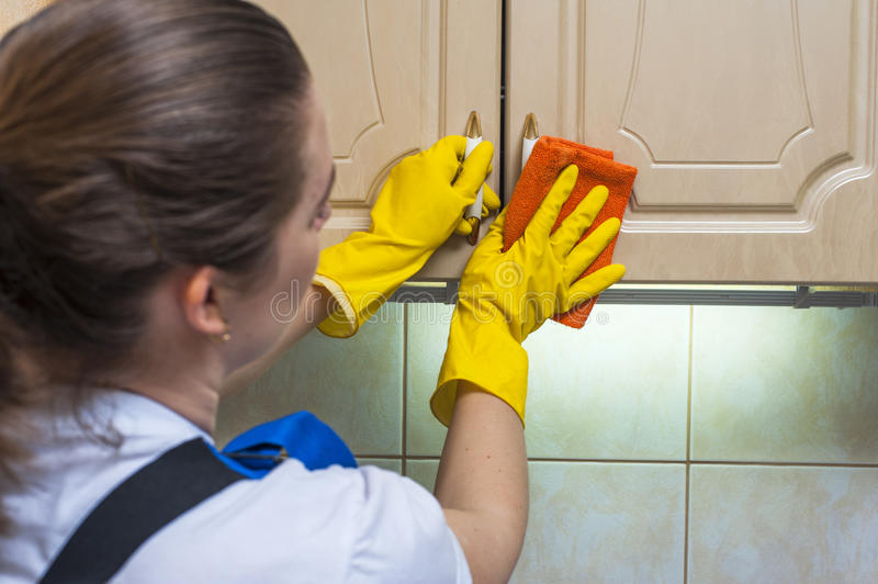 Female janitor scrubbing the kitchen cupboard with a rag royalty free stock image