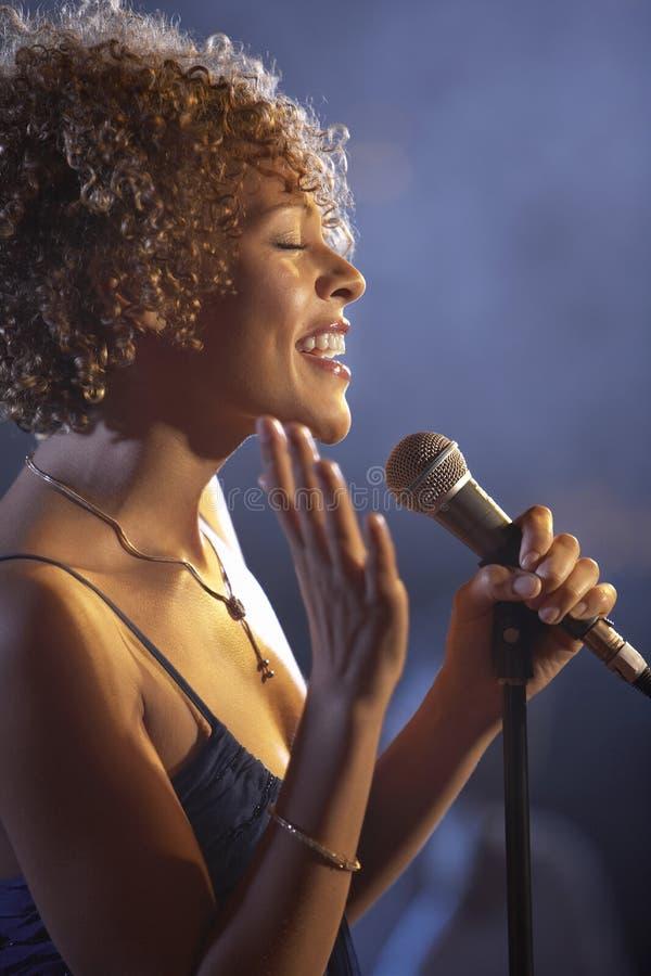 Female Jazz Singer On Stage. Closeup profile of a happy female jazz singer on stage royalty free stock photo