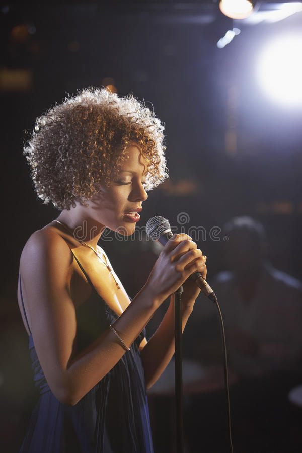 Female Jazz Singer On Stage. Profile shot of a female jazz singer on stage stock image