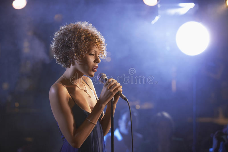 Female Jazz Singer On Stage. Profile shot of a female jazz singer on stage stock photography