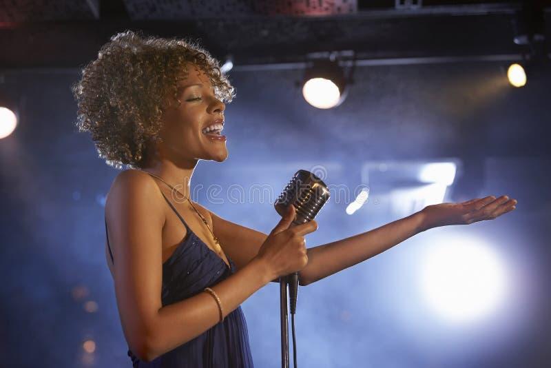Female Jazz Singer On Stage. Profile shot of a happy female jazz singer on stage royalty free stock image