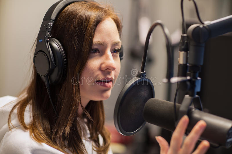 Female Jockey Talking On Microphone In Radio Studio stock photo