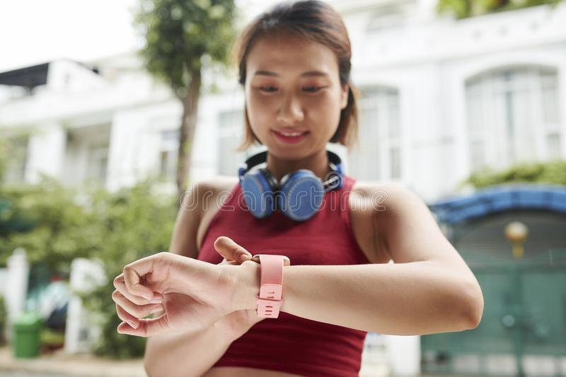 Female jogger checking pulse. Pretty female jogger checking pulse on her smart watch after training stock image