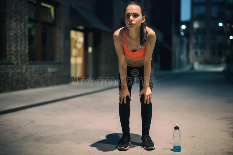 Female jogger in city night light. Female jogger resting under city night lamp royalty free stock images