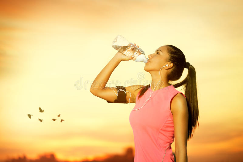 Female jogger drinking water. Outdoor stock image