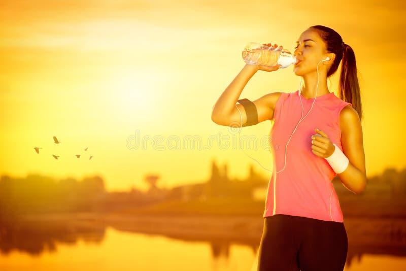 Female jogger drinking water. Thirsty female jogger drinking water from bottle royalty free stock image