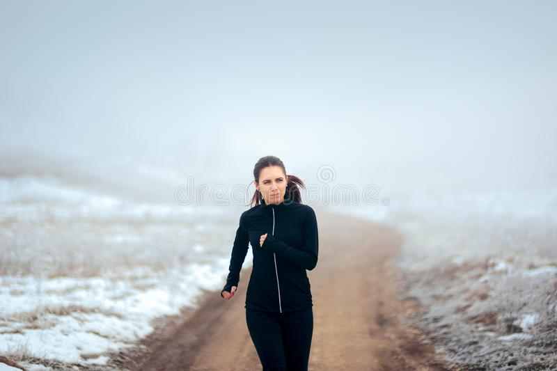 Tired Winter Runner Jogging Outside on Cold Weather. Female jogger feeling exhausted during outdoors workout session in winter cold stock photos