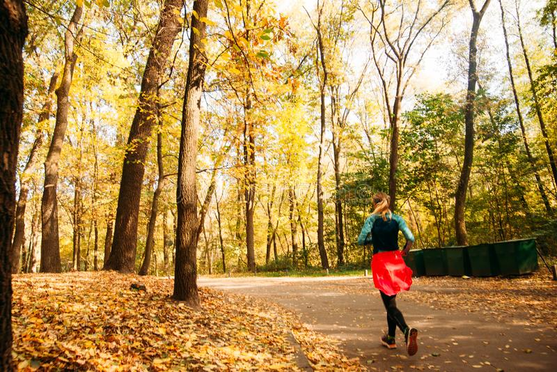 Female jogger. Fit young woman jogging in park running and enjoying a healthy outdoor lifestyle. Fitness runner girl in autumn. Forest with fall foliage. behind royalty free stock images