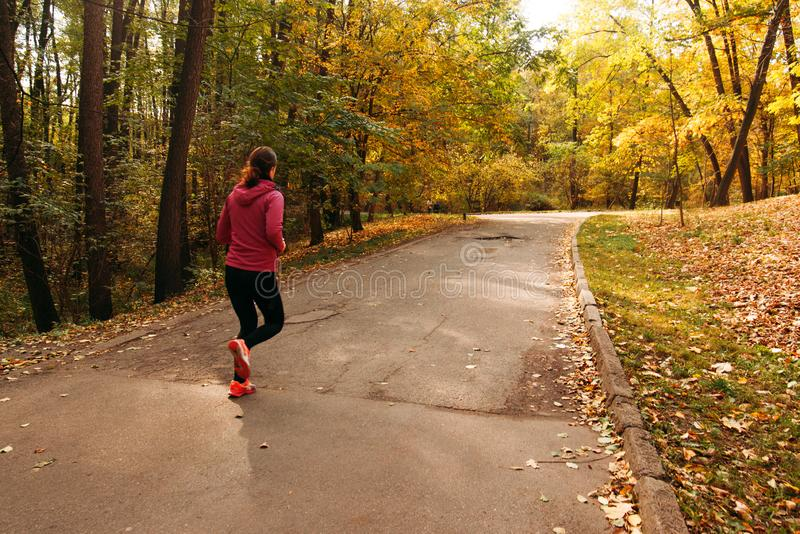 Female jogger. Fit young woman jogging in park running and enjoying a healthy outdoor lifestyle. Fitness runner girl in autumn royalty free stock photo