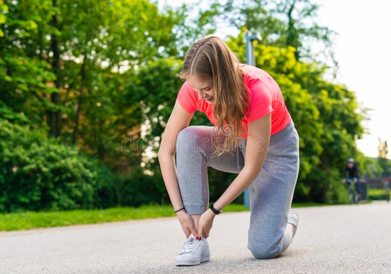 A female jogger has injured her foot and has a pain. A young female jogger has injured her foot and has a pain royalty free stock image