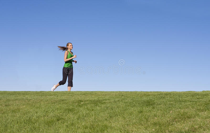 Female Jogger on the horizon. A female jogger runs along the grassy horizon royalty free stock image