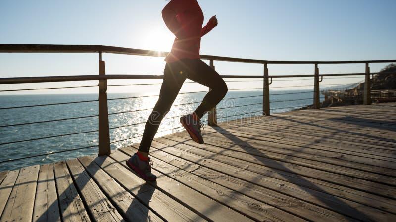 Female jogger morning. Sporty female jogger morning exercise on seaside boardwalk during sunrise royalty free stock image