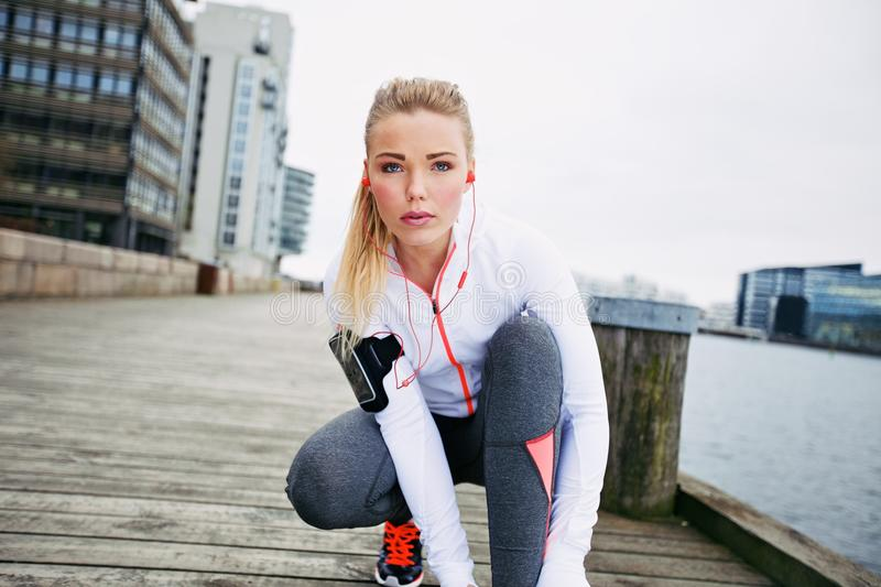 Female jogger preparing for second run. Fitness woman on boardwalk crouching to tie her shoelace looking at camera. Confident young female jogger training stock photo